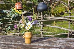 Blumenstrauß von Blumen im Vase auf rustikaler Tabelle Stockbild