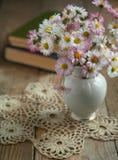 Blumenstrauß von Blumen mit Büchern. Stockbild