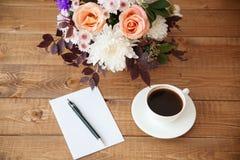 Blumenstrauß von Blumen und von Buchstaben auf dem Tisch Lizenzfreie Stockbilder