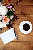 Blumenstrauß von Blumen und von Buchstaben auf dem Tisch Stockbild