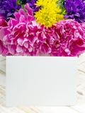 Blumenstrauß von Blumen und von leeren Blatt Papier auf hölzernen Planken Lizenzfreie Stockbilder