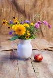 Blumenstrauß von Blumen und von reifem rotem Apfel Lizenzfreie Stockfotografie