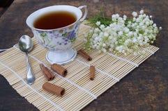 Blumenstrauß von Blumen und von Tasse Tee auf einem Holztisch Lizenzfreie Stockfotografie