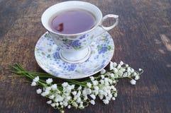 Blumenstrauß von Blumen und von Tasse Tee auf einem Holztisch Stockfotografie
