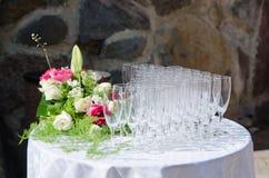 Blumenstrauß von Blumen und von Weingläsern für eine Hochzeit Lizenzfreies Stockfoto