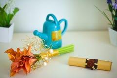 Blumenstrauß von Callalilien, von Teekanne und von Rolle auf dem Tisch Wenig Tabelle verziert mit Kerzenlicht, Vase und Büchern Stockbild