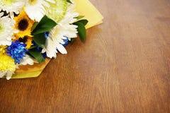 Blumenstrauß von den Blumen, die auf einer Holzoberfläche liegen Lizenzfreie Stockbilder