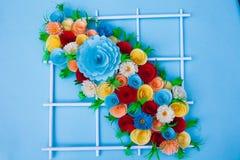 Blumenstrauß von den Blumen gemacht mit Papier auf einer blauen Oberfläche lizenzfreie stockbilder