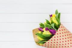 Blumenstrauß von den Frühlingsblumen eingewickelt im Papier mit Herzen auf weißem Holztisch Kopieren Sie Platz Lizenzfreies Stockbild