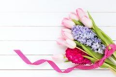 Blumenstrauß von den Frühlingsblumen verziert mit Band auf weißem hölzernem Hintergrund stockfoto