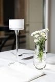 Blumenstrauß von den Gänseblümchen, die im Glasvase auf weißer Tabelle stehen Stockbilder
