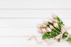 Blumenstrauß von den rosa Rosen verziert mit Spitze auf weißem hölzernem Hintergrund Lizenzfreies Stockbild
