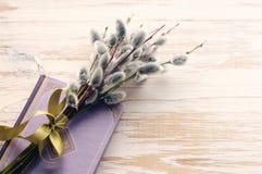Blumenstrauß von den Weidenniederlassungen und das Buch auf einer hellen Holzoberfläche Lizenzfreie Stockbilder