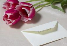 Blumenstrauß von drei roten Tulpen und der Buchstabe auf einer Tabelle lizenzfreies stockbild