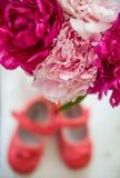 Blumenstrauß von Frühlingsblumen und von Schuhen der Kinder Lizenzfreies Stockfoto