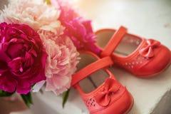 Blumenstrauß von Frühlingsblumen und von Schuhen der Kinder Lizenzfreies Stockbild