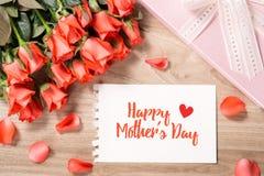 Blumenstrauß von frischen rosaroten Rosen mit Geschenk auf hölzernem Hintergrund Romantische mit Blumenanordnung mit Kartentext g Lizenzfreies Stockfoto
