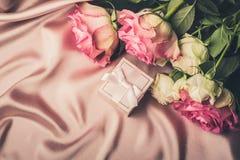Blumenstrauß von frischen Rosen und von Geschenk auf dem Hintergrund des Seidengewebes Kopieren Sie Platz Feierliches Konzept lizenzfreie stockbilder