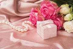 Blumenstrauß von frischen Rosen und von Geschenk auf dem Hintergrund des Seidengewebes Kopieren Sie Platz karte Feierliches Konze lizenzfreie stockfotografie