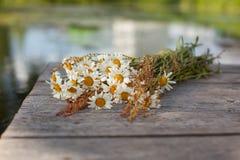 Blumenstrauß von Gänseblümchen auf den Brettern Stockfotografie