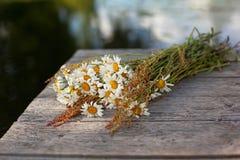 Blumenstrauß von Gänseblümchen auf den Brettern Stockfotos
