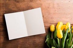 Blumenstrauß von gelben Tulpen und von leerer Grußkarte Lizenzfreie Stockbilder