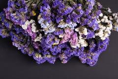 Blumenstrauß von getrockneten wilden Blumen auf einem schwarzen Beschaffenheitshintergrund der Draufsicht der hölzernen Planken d stockbild