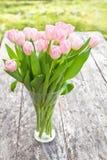 Blumenstrauß von hellrosa Tulpen auf der Eichenbrauntabelle in einem klaren g Lizenzfreie Stockfotos