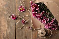 Blumenstrauß von Herbstblumen von Chrysanthemen im Kraftpapier auf einem braunen Holztisch stockbild