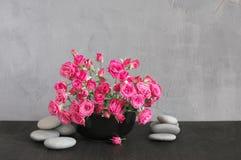 Blumenstrauß von hochroten Rosen auf Grau Lizenzfreie Stockfotografie