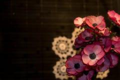 Blumenstrauß von künstlichen Blumen auf Häkelspitze Stockfotos