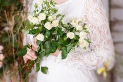 Blumenstrauß von kleinen Rosen in den Händen der Braut Stockbild