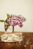Blumenstrauß von lila Frühlingsblumen auf hölzernem Lizenzfreie Stockfotos