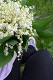 Blumenstrauß von Lilien in der Hand des Mädchens lizenzfreie stockfotografie