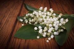 Blumenstrauß von Maiglöckchen auf einem Hintergrund von hölzernem Lizenzfreies Stockbild