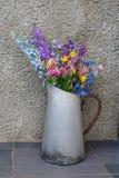 Blumenstrauß von mehrfarbigen Wildflowers in einem alten Metallkrug stockfotografie