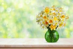 Blumenstrauß von Narzissen auf einem Holztisch Lizenzfreie Stockfotos