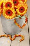 Blumenstrauß von orange Gerberagänseblümchen im silbernen Eimer auf hölzernem Vorsprung Stockbilder
