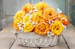 Blumenstrauß von orange Rosen in einem weißen Weidenkorb Lizenzfreie Stockfotos