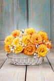 Blumenstrauß von orange Rosen in einem weißen Weidenkorb Stockfotografie
