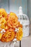 Blumenstrauß von orange Rosen in einem weißen Weidenkorb und in einer Weinlese bir Stockfotos