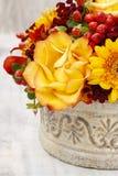 Blumenstrauß von orange Rosen und von Herbstpflanzen in Weinlese keramischem Vas Stockbild
