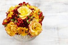 Blumenstrauß von orange Rosen und von Herbstpflanzen in Weinlese keramischem Vas Stockfotos