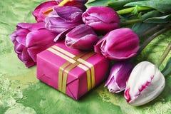 Blumenstrauß von purpurroten Tulpen und von Geschenkbox Stockfotografie