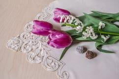 Blumenstrauß von purpurroten Tulpen und von weißer Hyazinthe mit Schokoladen Stockfotos
