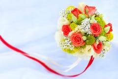 Blumenstrauß von Rad-Rosen auf dem weißen Hochzeitskleid Stockfotos