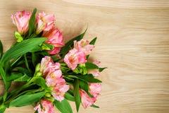 Blumenstrauß von rosa Alstroemeria auf hölzerner Platte Lizenzfreie Stockfotos