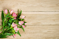 Blumenstrauß von rosa Alstroemeria auf hölzerner Platte Lizenzfreies Stockfoto