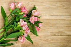 Blumenstrauß von rosa Alstroemeria auf hölzerner Platte Stockfotografie
