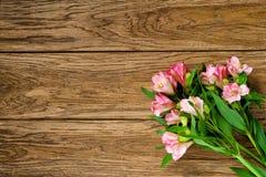 Blumenstrauß von rosa Alstroemeria auf hölzerner Platte Stockbild